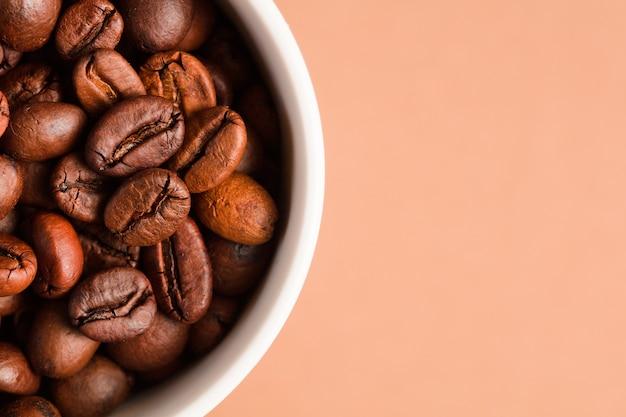 Кофейные зерна с керамической чашкой, коричневый фон.