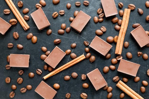 Кофе в зернах с кусочками шоколада и палочки корицы на черном фоне с плоским видом