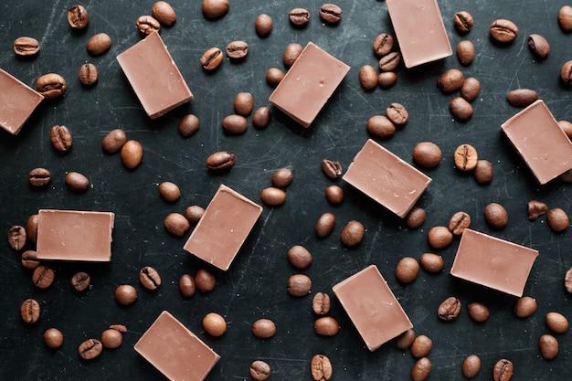 Кофе в зернах с кусочками шоколада на черном фоне с плоским видом