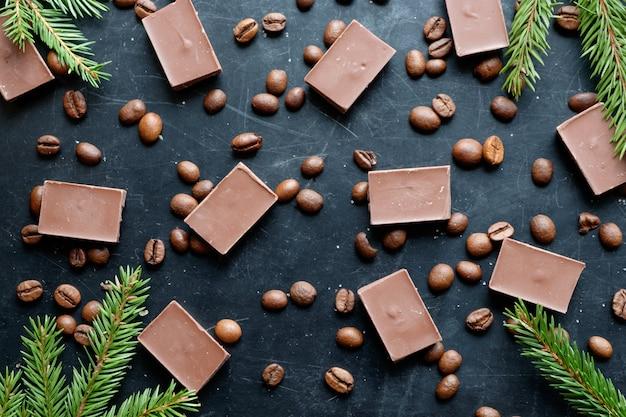 Кофе в зернах с кусочками шоколада на черном фоне плоский вид