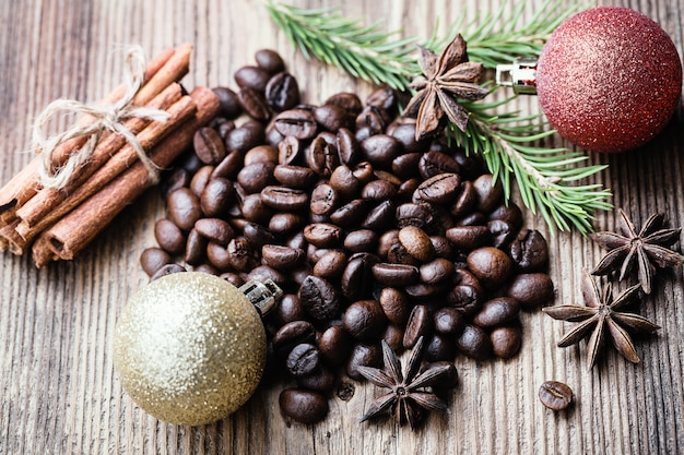 Coffee beans with cinnamon stick, aniseeds, fir-tree branch on wooden surface