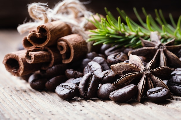 Coffee beans with cinnamon sticks, aniseeds, fir-tree branch on wooden surface.