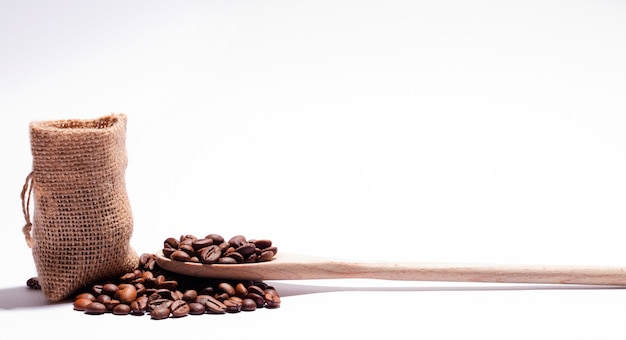 Кофейные зерна с тканевым мешком и деревянной ложкой с белым.
