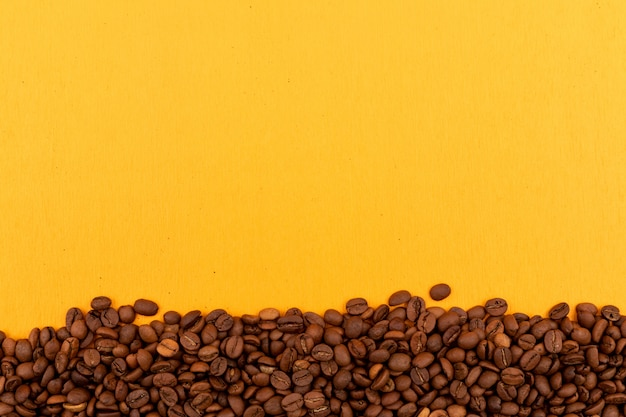 Coffee beans with copy space on yellow surface