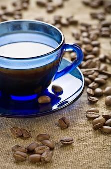 Кофейные зерна с чашкой на блюдце