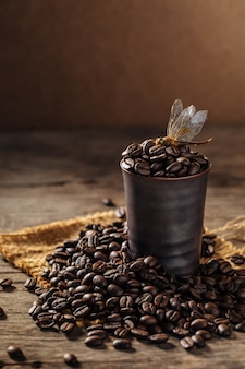 Coffee beans with dragonfly on wooden background