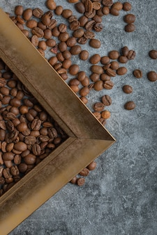 Coffee beans with empty frame on a marble surface.