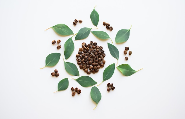 Кофейные зерна с листьями эвкалипта в виде круга на белой поверхности.