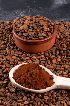 Chicchi di caffè con caffè macinato in un cucchiaio di legno