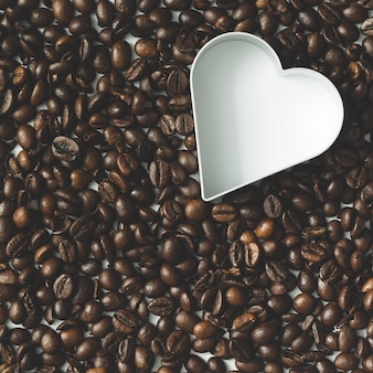 Coffee beans with heart cookie cutter. flat lay