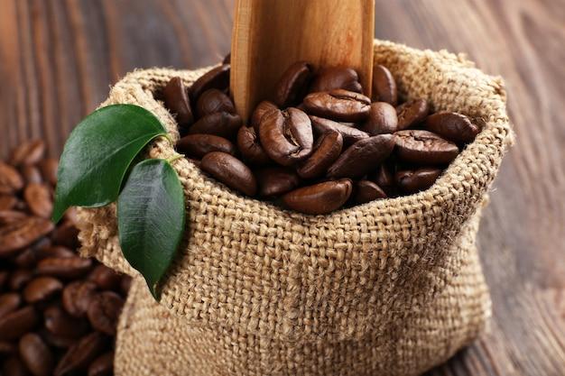 Кофейные зерна с листьями и ложкой в сумке на деревянном столе крупным планом