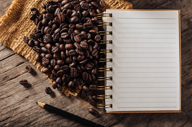 Coffee beans with note book on wooden background