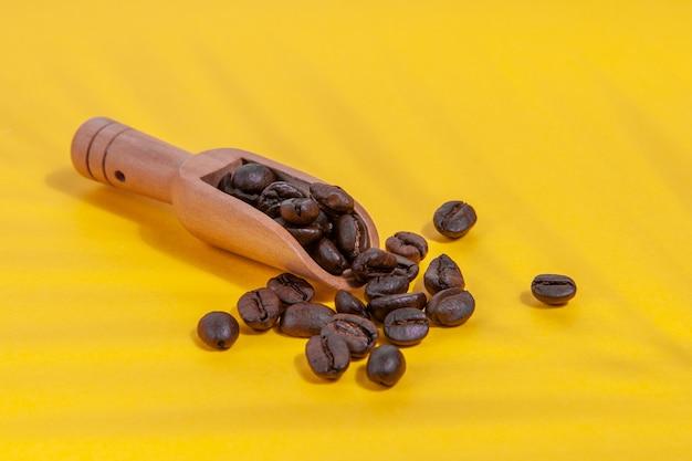 黄色の背景に散らばっているコーヒースプーンのヤシの木からの影とコーヒー豆。