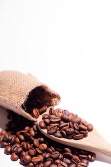 Кофейные зерна с белой деревянной ложкой и мешком