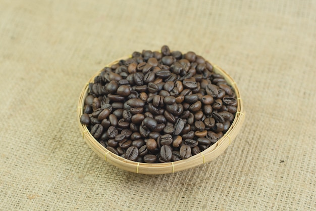 Coffee beans and wood bowl on jute bag background