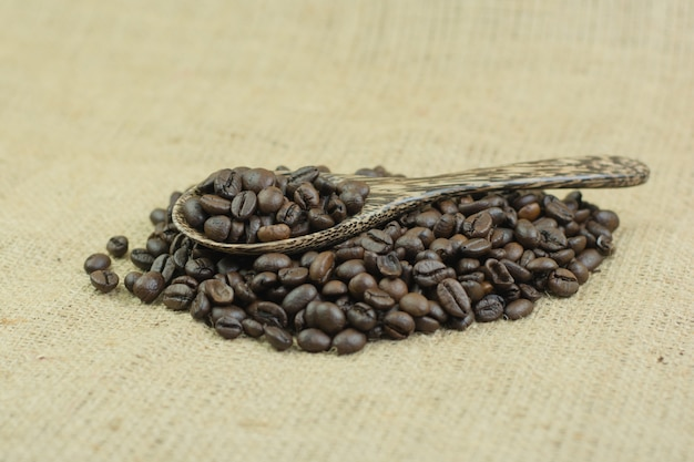 Coffee beans and wood spoon on jute bag background