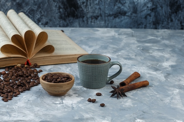 Coffee beans in a wooden bowl with book, cinnamon, cup of coffee high angle view on a light and dark blue marble background