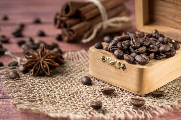 Coffee beans in a wooden box with cinnamon sticks and star anise on burlap napkins