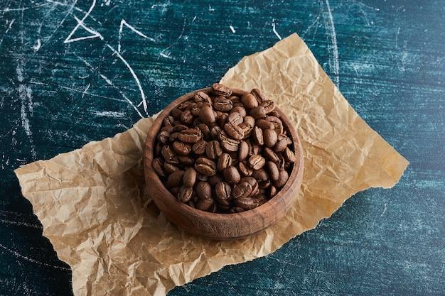 Chicchi di caffè in una tazza di legno su un pezzo di carta.