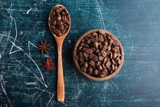 Chicchi di caffè in una tazza e un cucchiaio di legno.