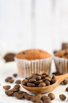 Chicchi di caffè sul cucchiaio di legno e cupcakes alla banana su un tavolo di legno bianco.