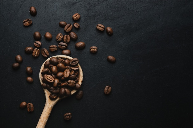 Coffee beans in wooden spoon on dark table. top view.
