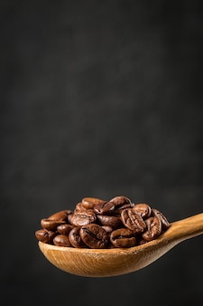 Coffee beans in a wooden spoon on gray background