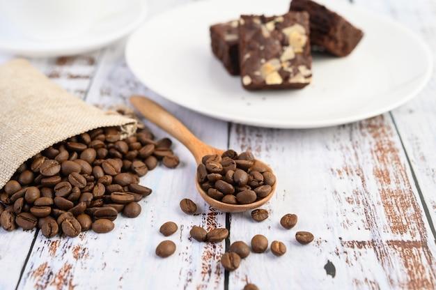 Chicchi di caffè sui sacchi di legno della canapa e del cucchiaio su una tavola di legno bianca.