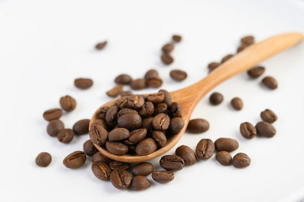 Coffee beans on wooden spoon on a white wood table.