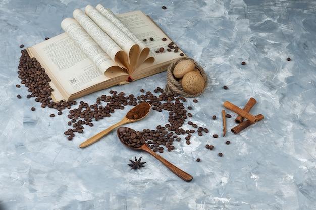 Chicchi di caffè in un cucchiaio di legno con caffè macinato, libro, spezie, biscotti ad alto angolo di visione su uno sfondo grigio sgangherato