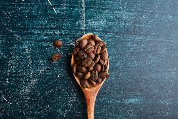 Coffee beans in a wooden spoon.