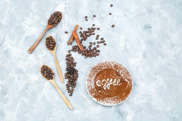 Chicchi di caffè in cucchiai di legno e bastoncini di cannella