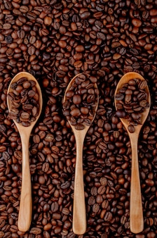 Coffee beans in wooden spoons on coffee beans top view