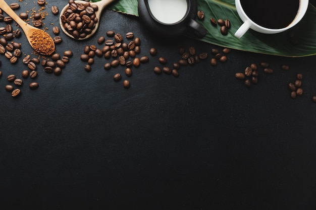 Coffee beans, wooden spoons and coffee espresso in cups