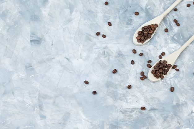 Coffee beans in wooden spoons flat lay on a grey plaster background