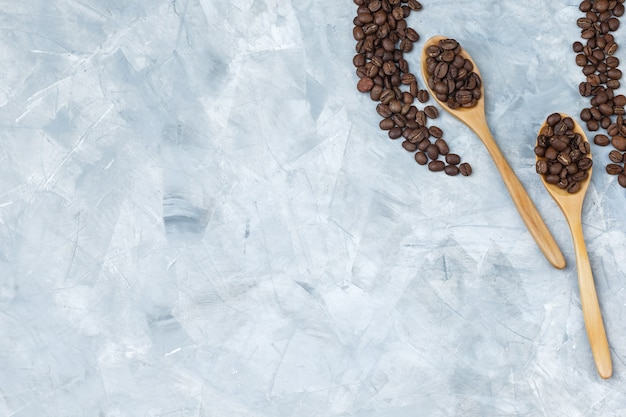 Coffee beans in wooden spoons on a grey plaster background. flat lay.