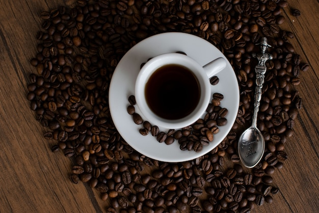 Coffee beans on a wooden table, white coffee utensils, a cup of espresso