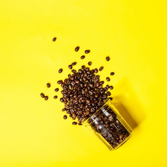Coffee beans on yellow table, flat lay, top view