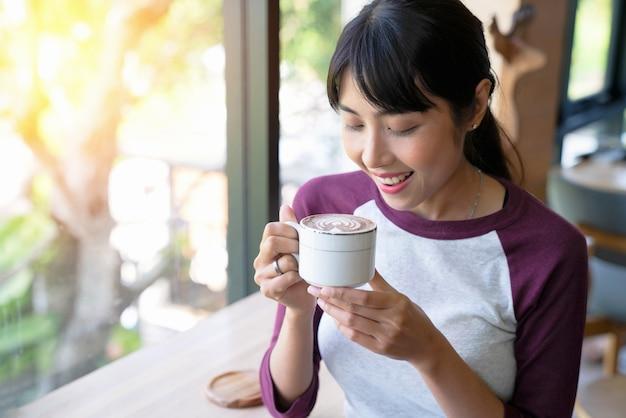 コーヒー。カフェでコーヒーを飲む美しい女の子。ホットビーヴのカップを持つ美人モデルの女性
