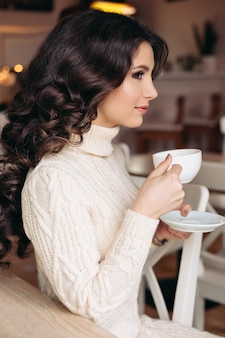 Coffee. beautiful girl drinking tea or coffee. cup of hot beverage. brunette in a cafe drinking tea, eating sweets, reading a book, beautiful eyes and gorgeous makeup, wavy hair.