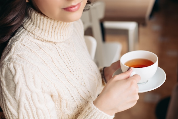 Кофе. красивая девушка, пить чай или кофе. чашка горячего напитка. брюнетка в кафе пьет чай, ест сладости, читает книгу, красивые глаза и шикарный макияж, волнистые волосы.