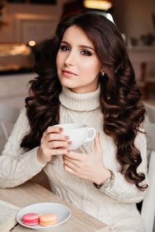 커피. 차 또는 커피를 마시는 아름 다운 소녀. 뜨거운 음료 한잔. 차를 마시고, 과자를 먹고, 책을 읽고, 아름다운 눈과 화려한 메이크업, 물결 모양의 머리카락을 마시는 카페에서 갈색 머리.