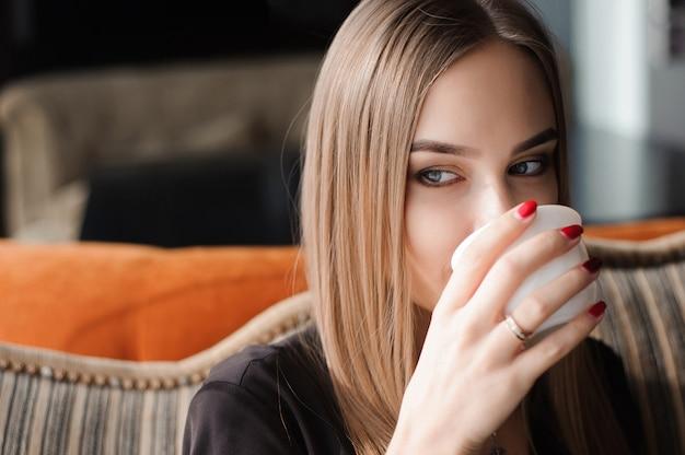 Кофе. красивая девушка пьет чай или кофе в кафе
