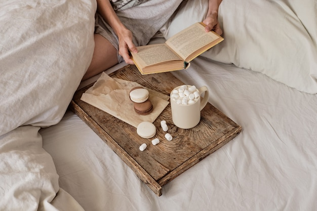 Coffee in bed. shapely female legs in warm socks, wooden tray for breakfast in bed. two cups of coffee and marshmallows. the concept of cozy home. top view