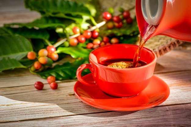 Coffee being poured into red cup with coffee seeds and leaves over wooden table.