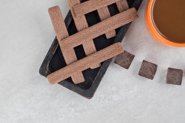 Caffè, biscotti e cioccolato fondente su superficie di marmo