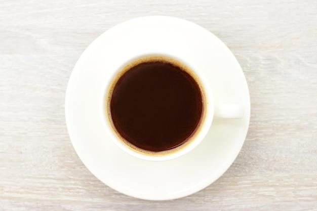 白いカップのコーヒーブラックホットエスプレッソ、素朴な木製テーブルの受け皿。閉じる。上面図。選択的なソフトフォーカス。テキストコピースペース。
