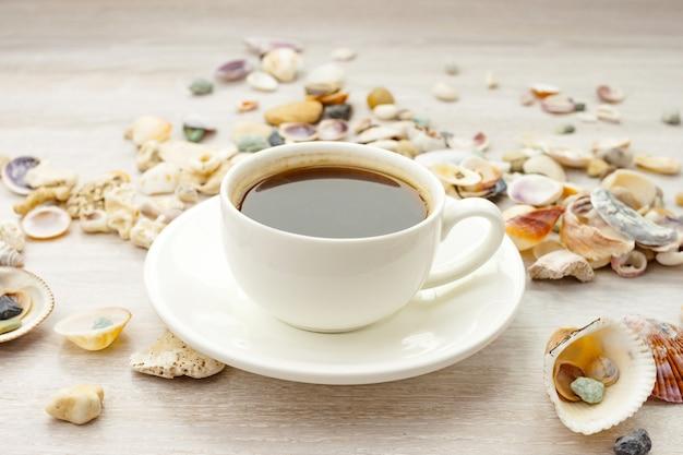 白いカップのコーヒーブラックホットエスプレッソ、素朴な木製のテーブルの貝殻と小石の受け皿。閉じる。側面図。選択的なソフトフォーカス。テキストコピースペース。