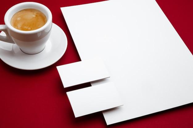 コーヒー、空白のチラシのポスター、赤い背景の上に浮かぶカード。広告、画像、またはテキスト用のオフィススタイルのモダンなモックアップ。デザイン、ビジネス、財務のコンセプトのための空白の白いコピースペース。