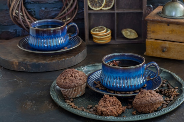 Coffee in blue ceramic cups, muffins and an old coffee grinder close up